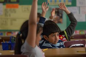 Students raising hands in ESL classroom