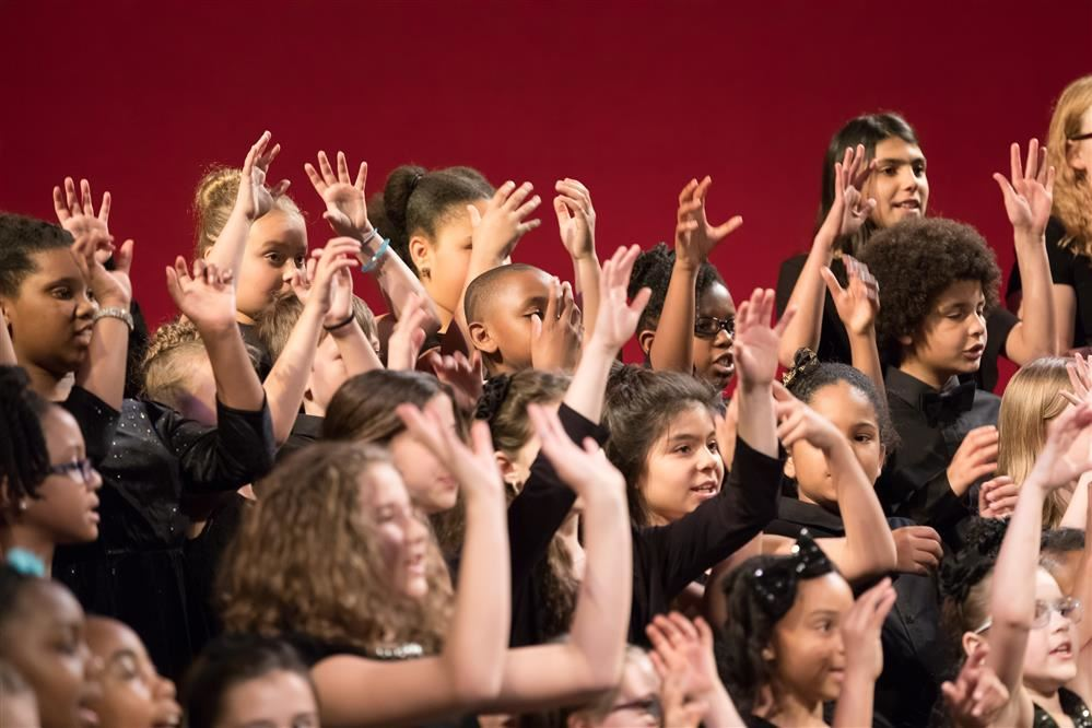 Young students in choir raising hands