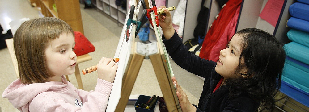 Two young students drawing on art easel