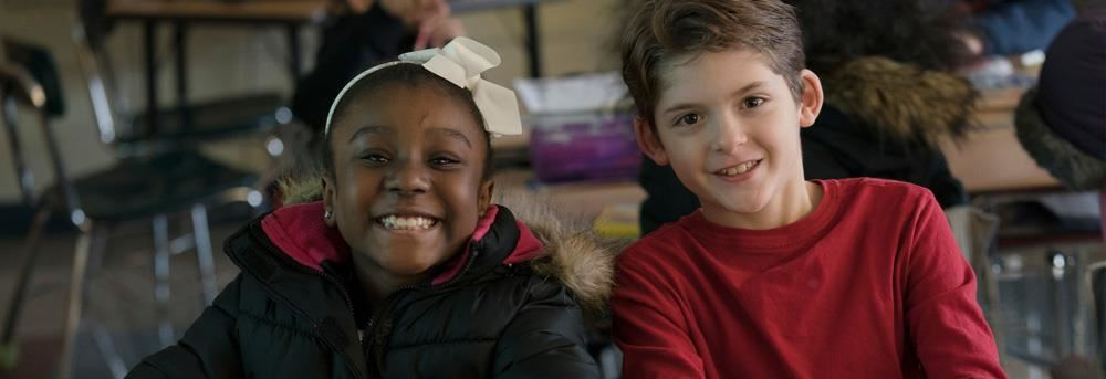 Two young students smiling in classroom