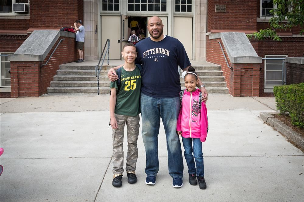 Dad standing outside school with two young children