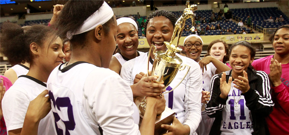 High School Girls holding trophy on basketball court
