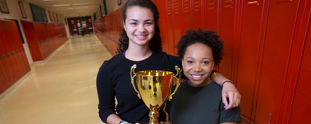 Two High School Students hold trophy in hallway