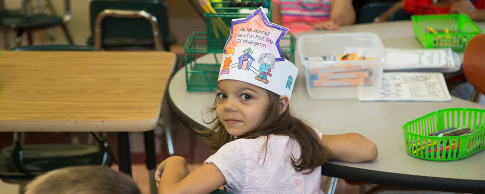 Kindergarten Student sitting at desk with paper crown that says Hip Hip Hooray I had a fun first day