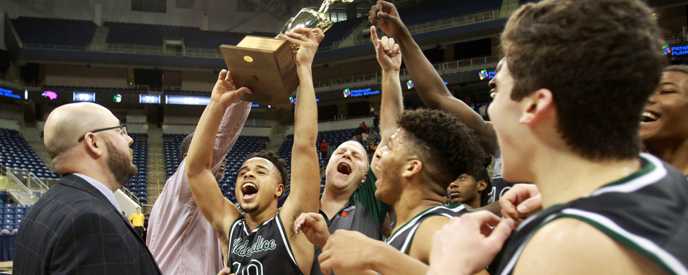 Group of High School Male Basketball Players hold up trophy after win