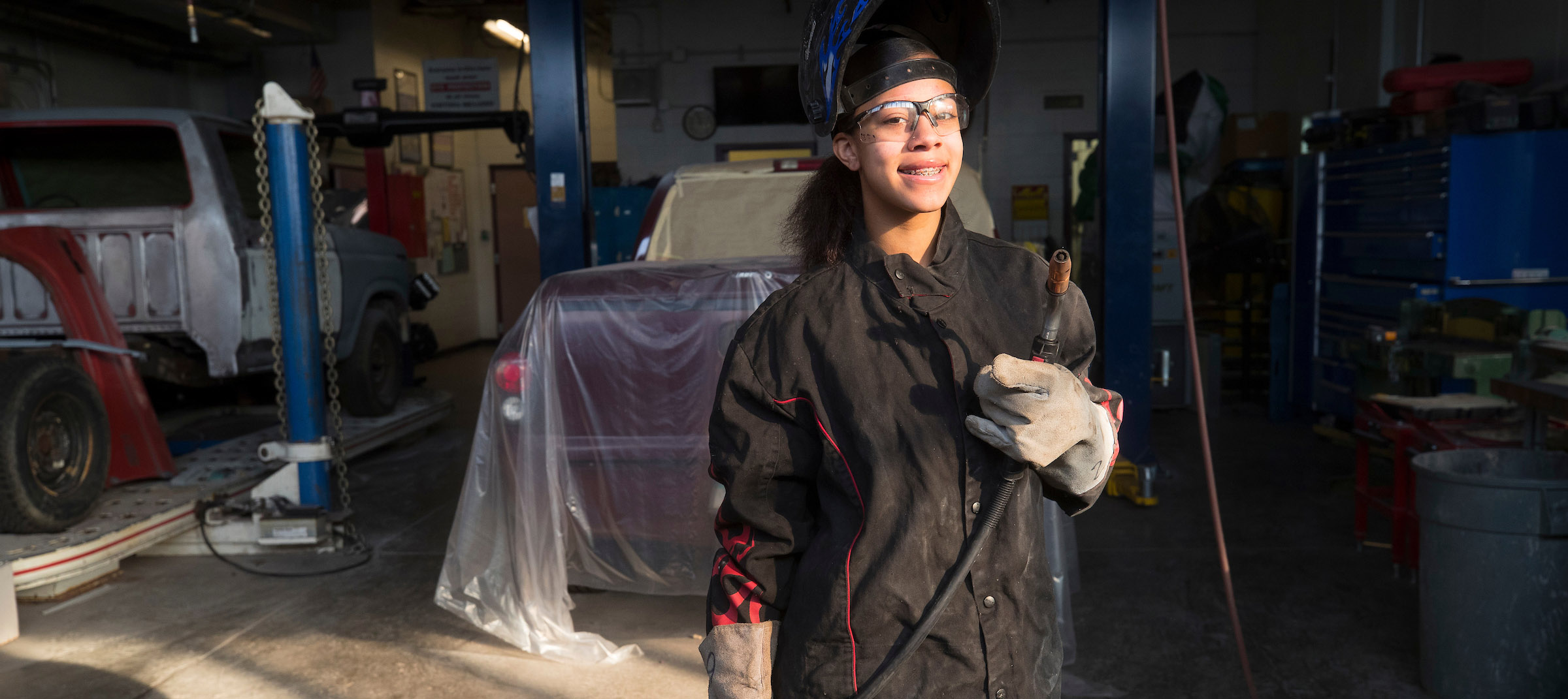 Student in automotive classroom posing