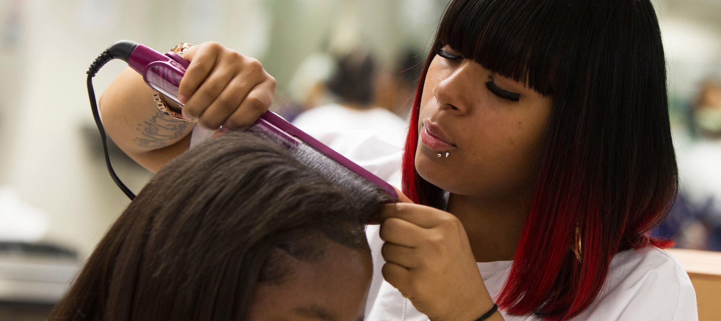Student in cosmetology classroom straightening hair