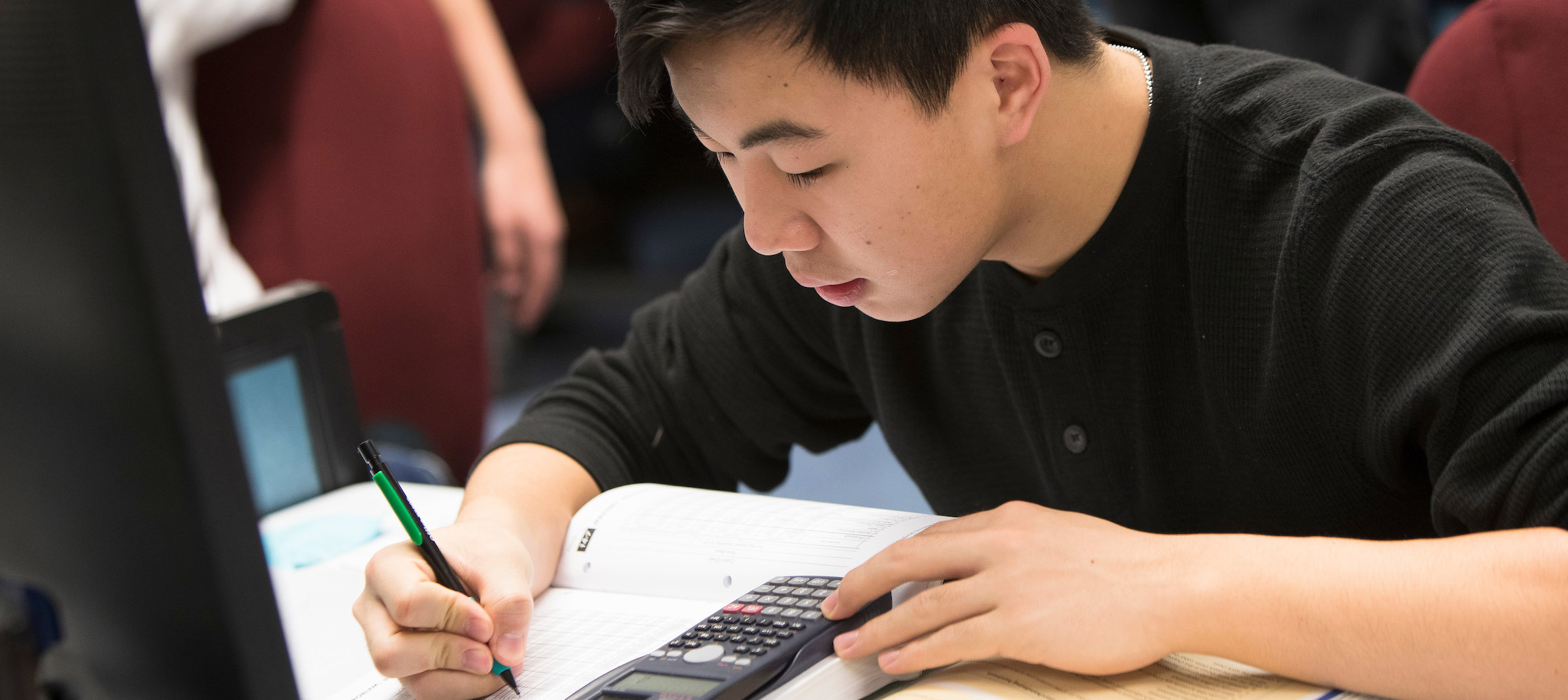 Students looking at book with calculator